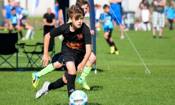 Scène de tournoi de football : un joueur guide le ballon lors de la mini-coupe du monde des amis du ballon.